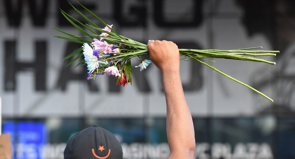 """Un manifestante sostiene flores sobre su cabeza durante una protesta de """"Black Lives Matter"""" cerca del Barclays Center en el distrito de Brooklyn de la ciudad de Nueva York, indignado después de que George Floyd, un hombre afroamericano desarmado, muriera mientras era arrestado por la policía en Minneapolis. (Foto: AFP/Angela Weiss)"""
