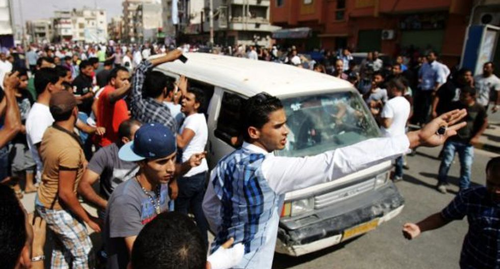 Los residentes de reúnen en torno a un coche-bomba que explotó en un hospital local en  Benghazi. (Foto: AFP)