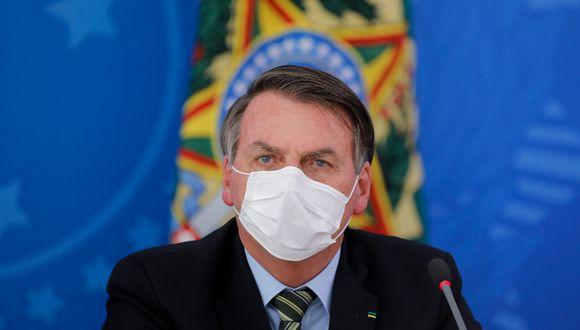 El presidente de Brasil, Jair Bolsonaro, se cubre la cara con una máscara facial durante una conferencia de prensa sobre la pandemia de coronavirus. (AFP).