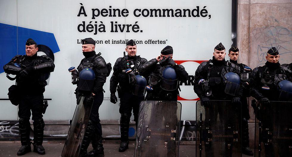 La policía antidisturbios francesa hace guardia mientras los bomberos recorren las calles parisinas exigiendo mejoras en sus condiciones de trabajo. (Foto: EFE)
