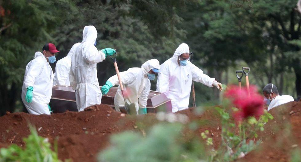 Empleados del servicio funerario entierran a una víctima de COVID-19 en el cementerio de Vila Formosa, situado en Sao Paulo. (EFE/FERNANDO BIZERRA).