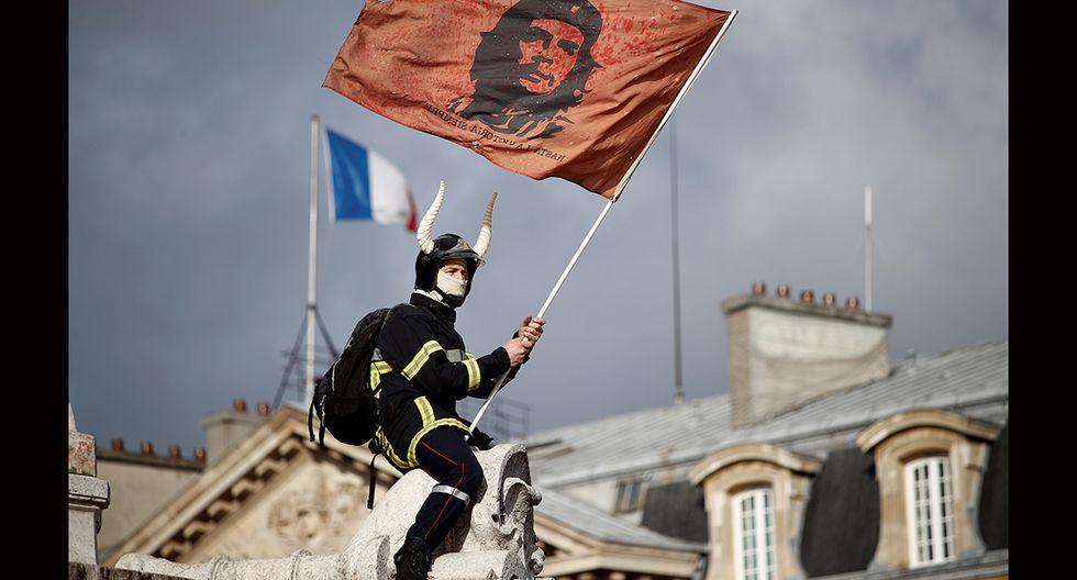 Bombero encima de un monumento agita una bandera del Che Guevara. (Foto: EFE)