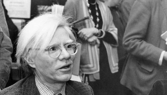 """El artista pop y cineasta estadounidense Andy Warhol fimando copias de su libro """"From A t B and back again"""" en Londres en noviembre de 1975. (Foto: AFP)"""