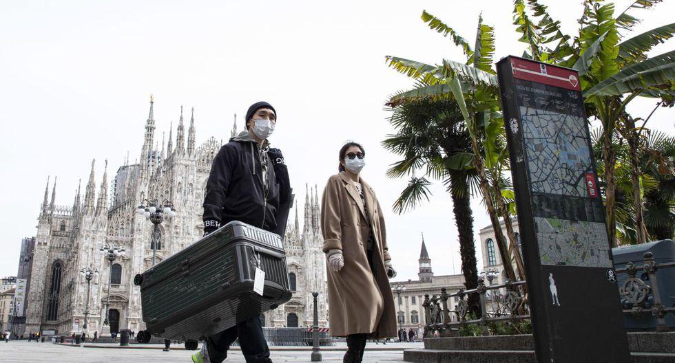 Los turistas usan máscaras faciales protectoras mientras caminan por la casi vacía Piazza del Duomo ('Plaza de la Catedral') en Milán, Italia. (EFE).