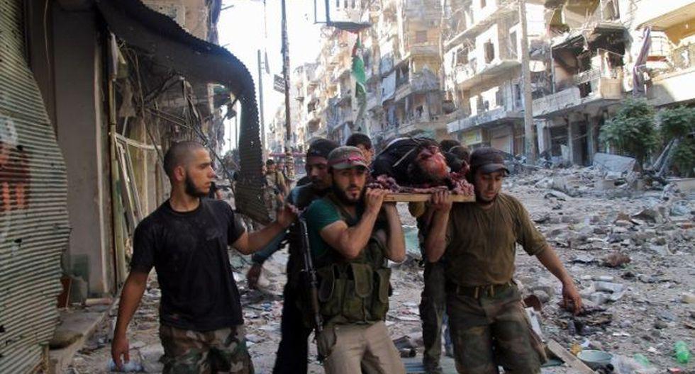 Soldados rebeldes cargan a uno de sus camaradas muertos en Aleppo, Siria (Foto: AFP)