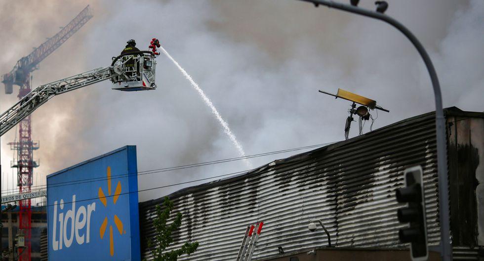 Bomberos apagan un incendio en el supermercado Líder. (Foto: AFP)