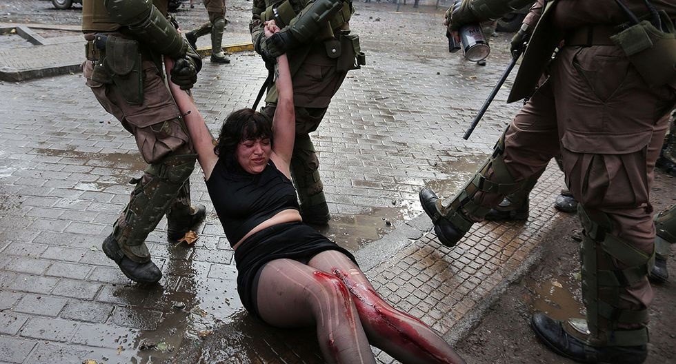 Una mujer manifestante es arrastrada por la policía en la Plaza Italia de Santiago de Chile. (Foto: EFE)