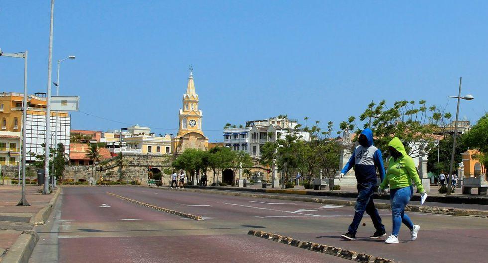 Una pareja totalmente abrigada cruza una calle en Cartagena (Colombia). (EFE/ Ricardo Maldonado Rozo).