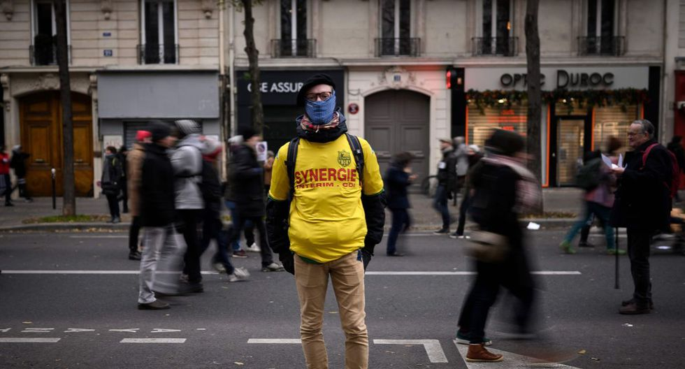 Harold, un fisioterapeuta de 25 años posa para una foto durante una manifestación para protestar contra las revisiones de las pensiones, en París, el 5 de diciembre de 2019 como parte de una huelga general nacional. (AFP)