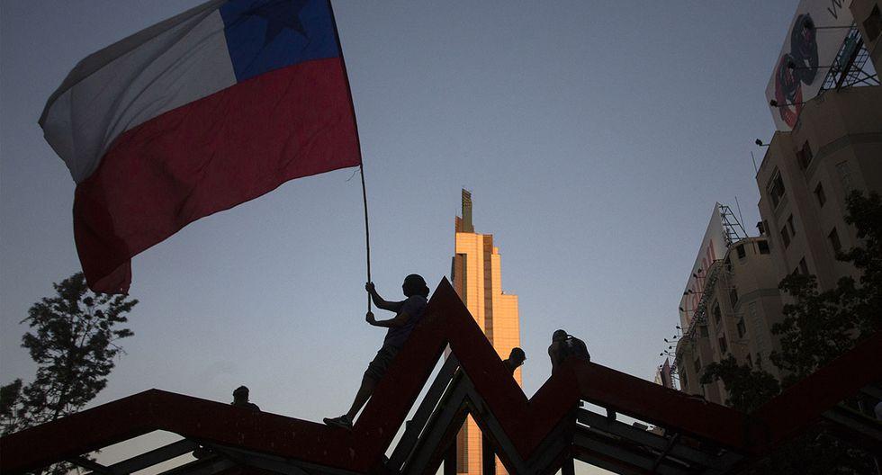 Un manifestante ondea una bandera nacional chilena durante una protesta contra el gobierno en Santiago. (Foto: AFP)