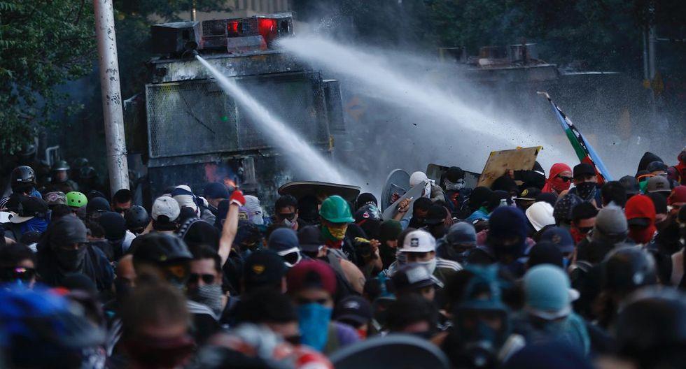 """Manifestantes se enfrentan con Carabineros durante una nueva jornada de protestas en la Plaza Italia, rebautizada popularmente como """"Plaza Dignidad"""", en Santiago. (Foto: EFE)"""