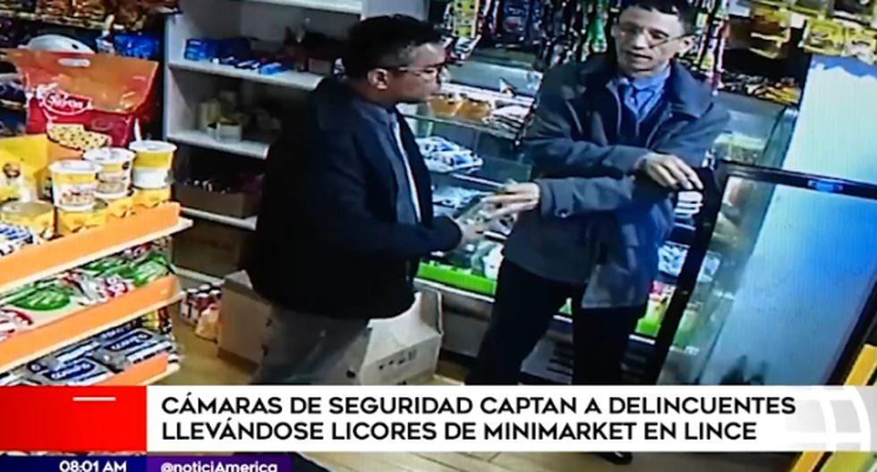 En las imágenes difundidas por América Noticias, se observa como dos hombres vestidos de terno y corbata ingresan a la tienda y hacen el ademan de que van a comprar. (América Tv)