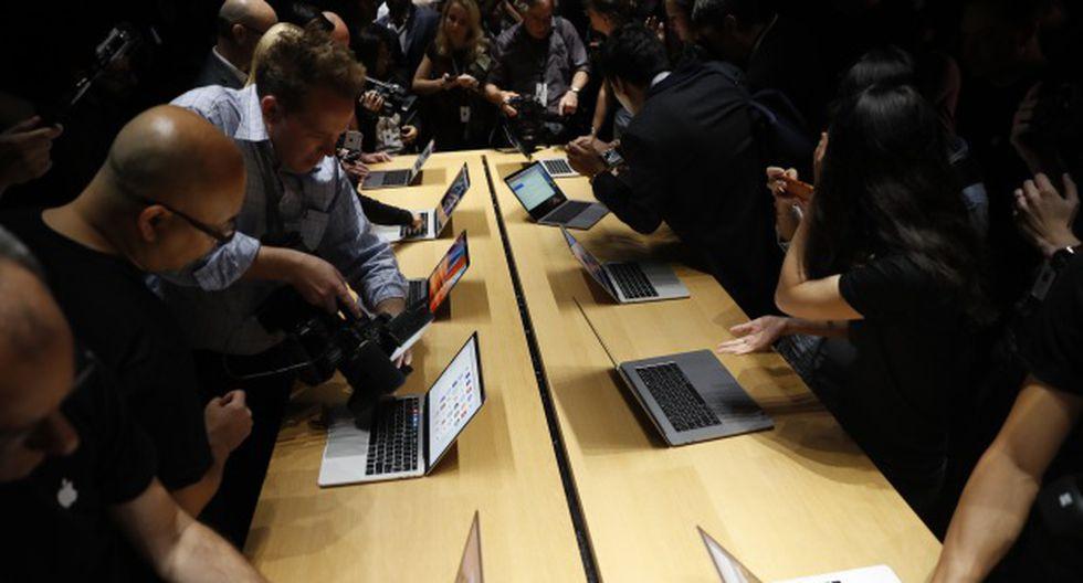 Miembros de los medios de comunicación se reúnen alrededor de una mesa que muestra la computadora portátil Apple MacBook Pro en 2016. (Foto: AFP)