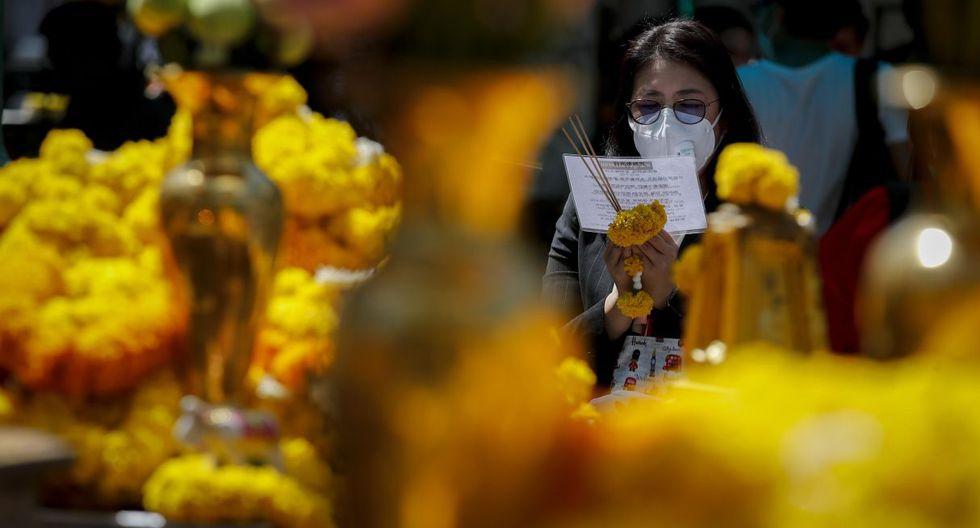 Una mujer que lleva una máscara de protección ofrece sus oraciones a Brahma, el Dios hindú de la creación, en el Santuario de Erawan en Bangkok. (EFE).