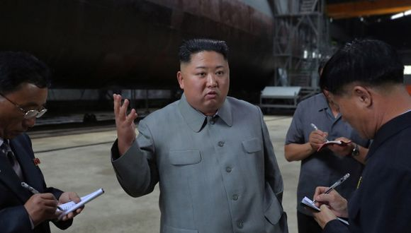 Kim Jong-un habla con funcionarios luego de realizar una ronda del submarino recién instalado en un lugar no revelado en Corea del Norte. (Foto: EFE)