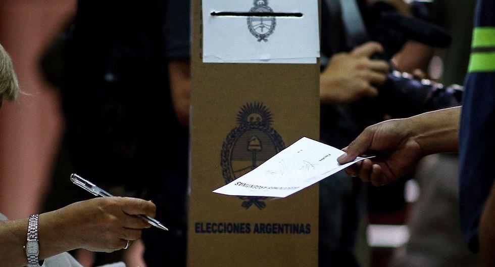 Una hombre recibe un sobre para emitir su voto en las elecciones presidenciales de Argentina. (Foto: EFE)