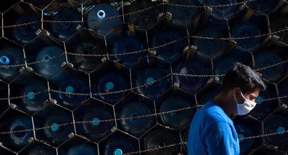 Un hombre usa una máscara facial como medida de precaución contra la propagación del nuevo coronavirus, mientras pasa por un camión que transporta latas de agua potable en Caracas. (Foto: AFP/Cristian Hernández)