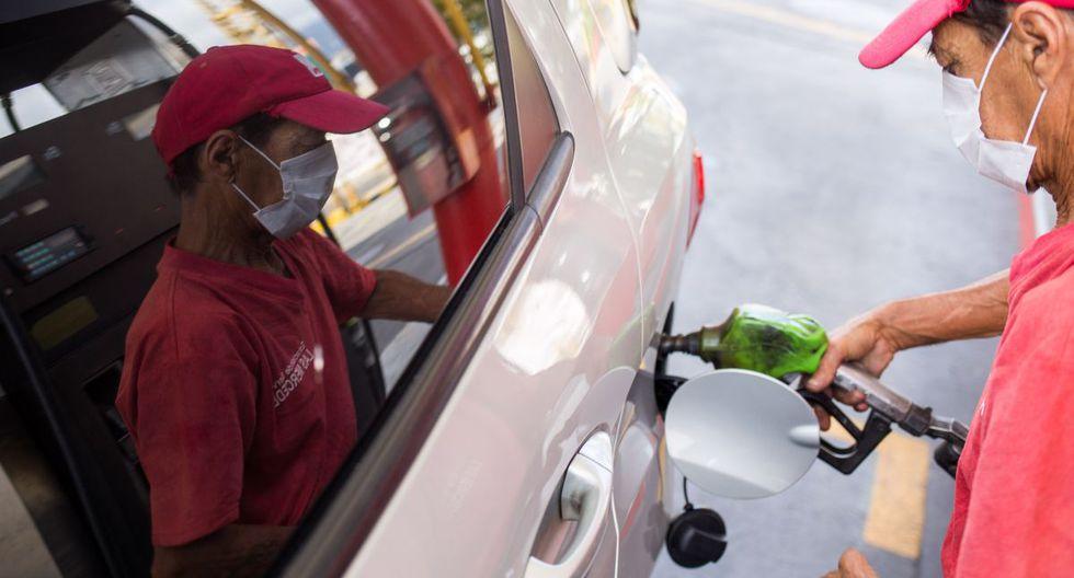 Un trabajador de una estación de servicio llena el tanque de un automóvil con gasolina con una máscara facial como medida de precaución contra la propagación del nuevo coronavirus, en Caracas. (Foto: AFP/Cristian Hernández)