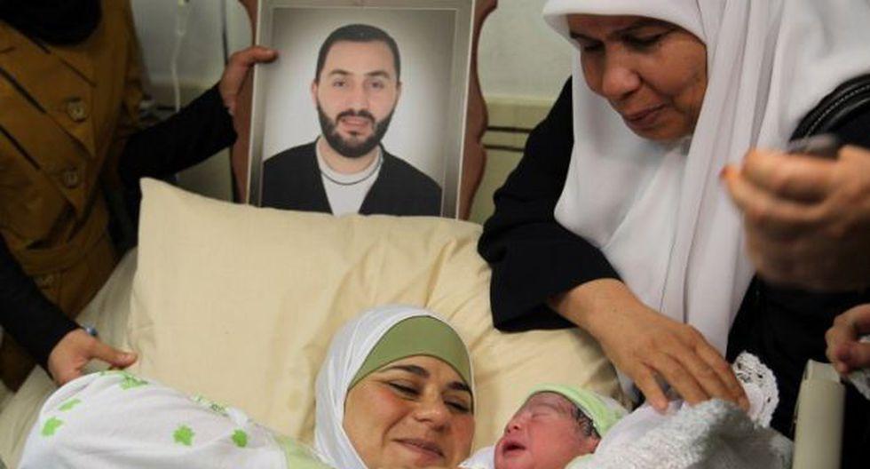 Dallal Ziben junto a su bebé Mohanad y una foto del padre (Foto: AFP)