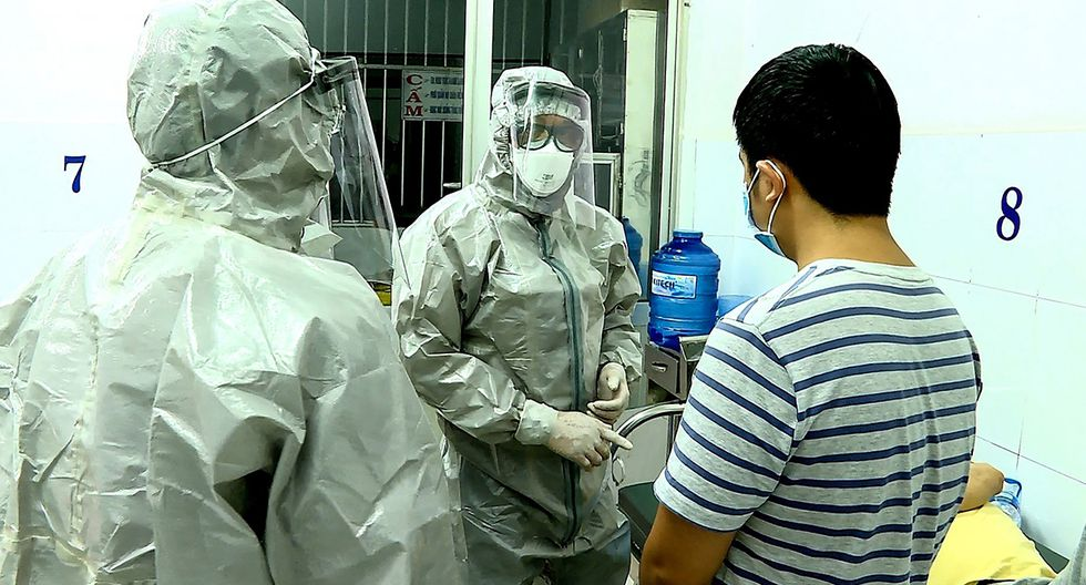 El personal médico que usa trajes de protección interactúa con dos pacientes infectados con el coronavirus de Wuhan. (Foto: AFP)