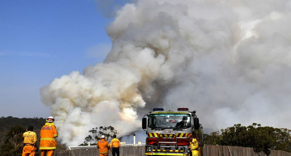 Firefighters work as smoke rises from a bushfire in Penrose, in Australia's New South Wales state on January 10, 2020. - High temperatures and strong winds were expected to fan massive bushfires blazing across southeastern Australia on January 10, as authorities issued new emergency warnings after several days of cooler conditions brought some reprieve to affected communities. (Photo by SAEED KHAN / AFP)