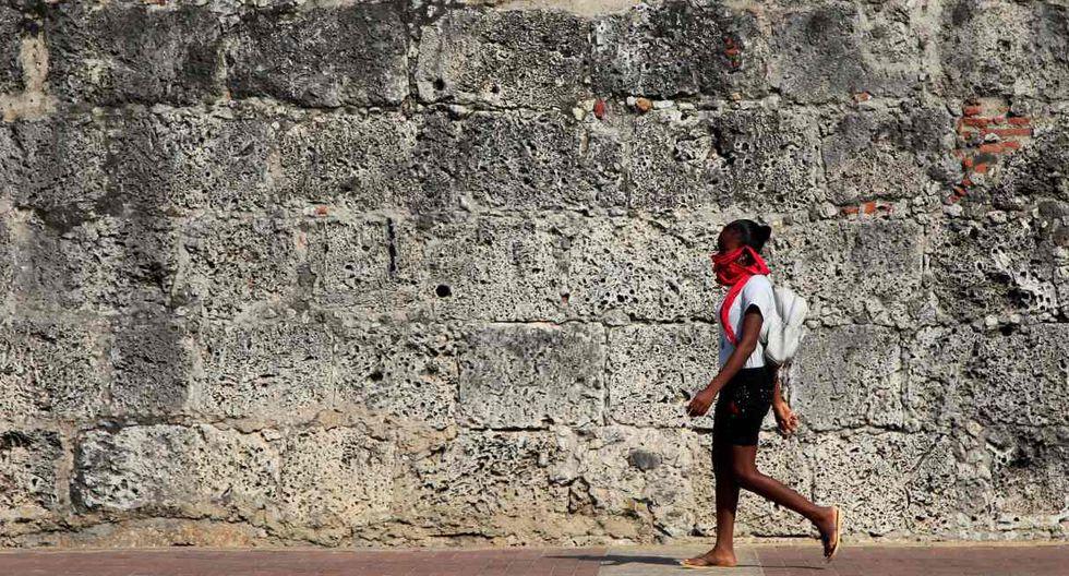 Una joven camina por la cera de una muralla en Cartagena (Colombia). El aislamiento social obligatorio por coronavirus es una medida drástica que ha sido tomada por varios países del mundo. (EFE/ Ricardo Maldonado Rozo).
