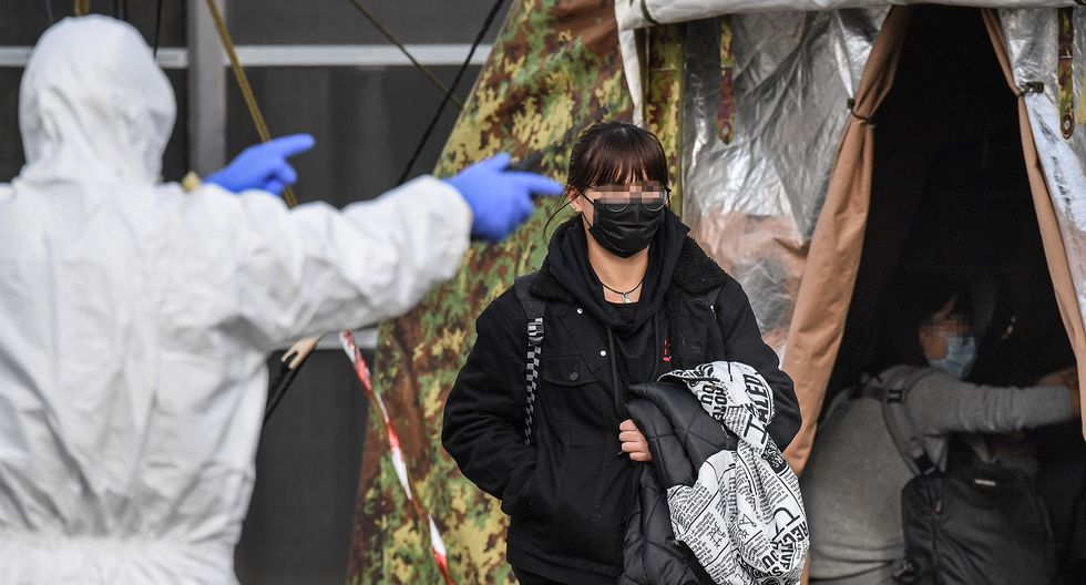 An Italian citizen (C) repatriated from the coronavirus hot-zone of Wuhan is directed to a health control zone after landing at the Mario De Bernardi military airport in Pratica di Mare, south of Rome, on February 3, 2020 prior to be placed in quarantine at the nearby Cecchignola center. (Photo by ANSA / AFP)