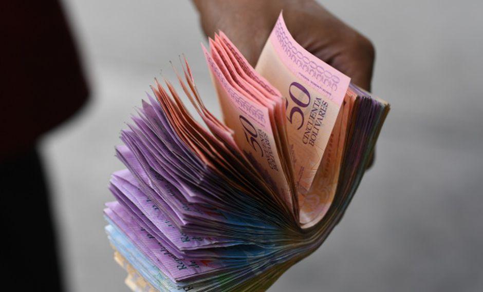 Los trabajadores ingresan, además, mensualmente, un bono de alimentación de 25.000 bolívares (2,21 dólares), que no genera pasivos laborales. En la foto, un hombre muestra bolívares, la moneda nacional venezolana. (Foto: AFP)