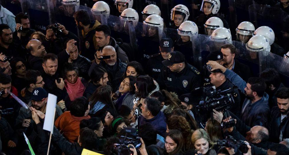 Los manifestantes reaccionan cuando la policía antidisturbios bloquea el acceso a las activistas por los derechos de las mujeres durante una marcha a la plaza Taksim en Estambul. (Foto: AFP)