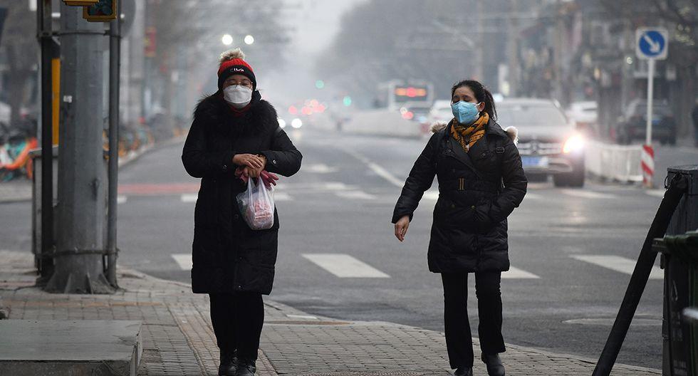 Las mujeres usan mascarillas para protegerse contra el coronavirus COVID-19 mientras caminan por una acera en Beijing. (Foto: AFP)